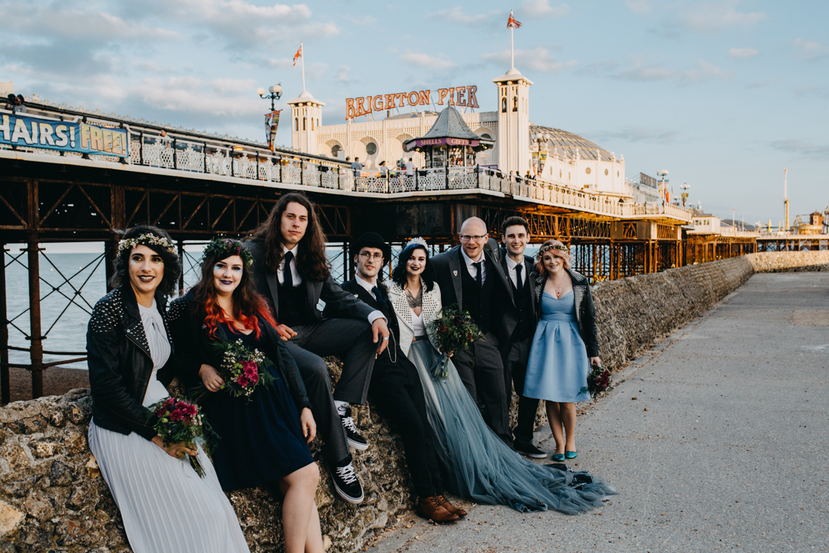 alternative bride and groom with bridesmaids and ushers by brighton pier during their alternative brighton beach wedding