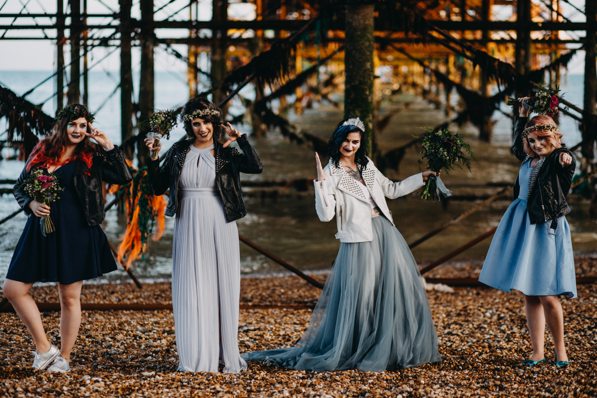 alternative goth bride with awesome bridesmaids under brighton pier on brighton beach by lex fleming photo
