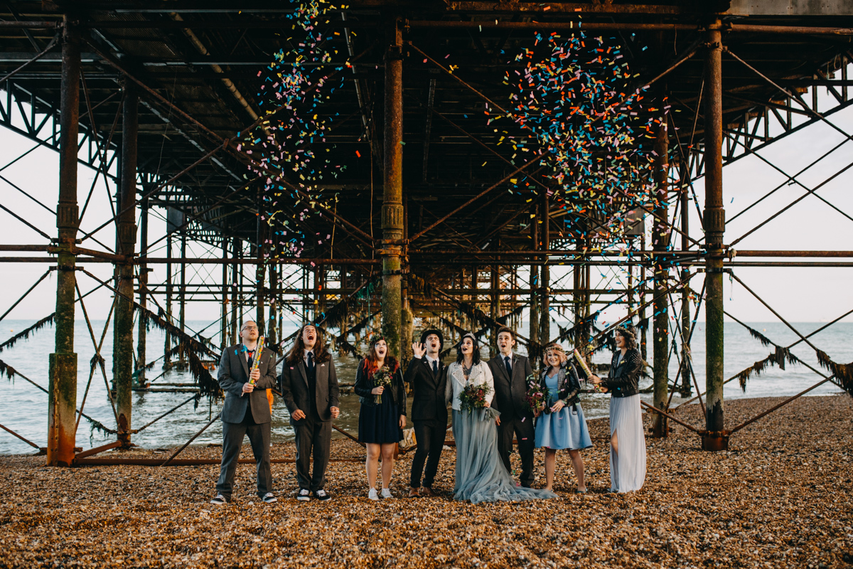 alternative wedding party setting off confetti cannons on brighton beach under brighton pier by lex fleming photography