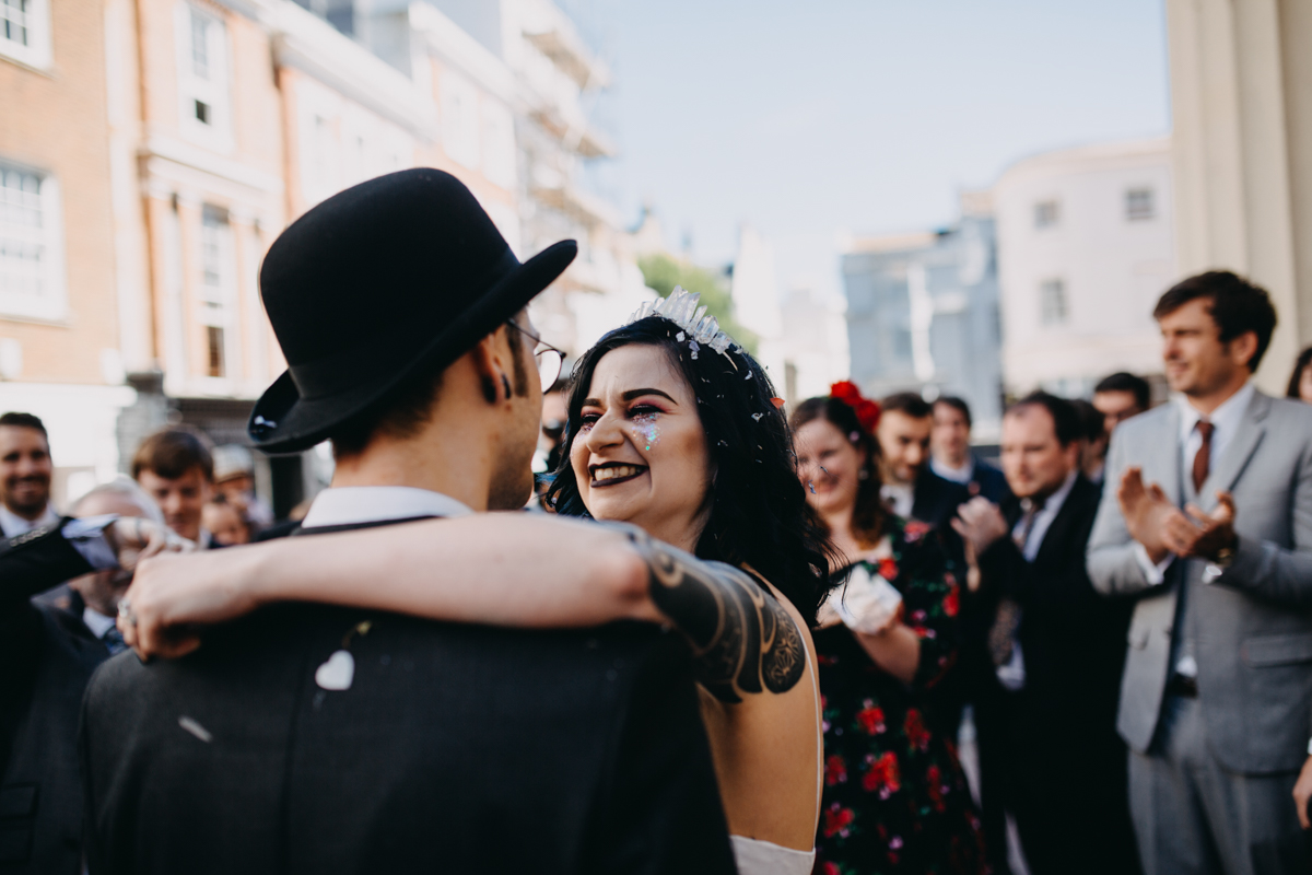 alternative tattooed bride hugging alternative groom at brighton town hall wedding