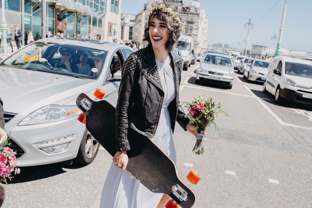 alternative bridesmaids wearing asos dress leather jacket carrying long board skateboard