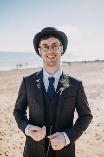 alternative groom in bowler hat on brighton beach